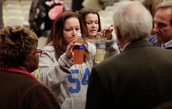 Flint residents show public officials water samples from their homes